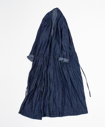 リネンデニムの生地を贅沢に使いウエストの切り替えからたっぷりギャザーを寄せた一枚でも羽織りとしても使える「リネンデニムカシュクールワンピース」。