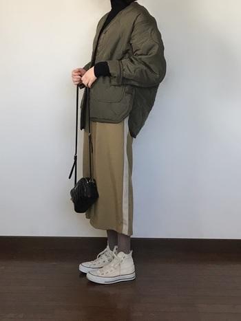サイドラインが入ったカーキのスカートに、ミリタリージャケットを羽織った同系色コーデ。配色が抑えられていることで、統一感が出て、スポーツミックスでも落ち着いた印象になっています。