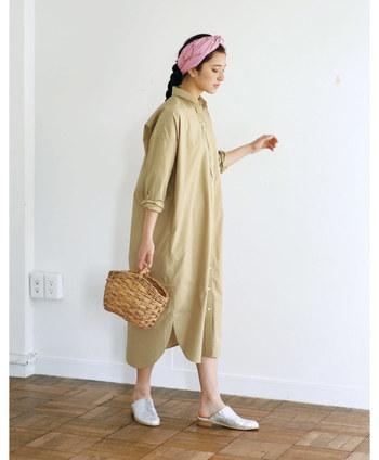 ゆったりとしたサイズ感のベージュシャツワンピースは、そのまま着てもサマになるアイテム。ボタンを上までしっかり留めて、ヘアバンドやカゴバッグなどの小物で上手にこなれ感をプラスしています。