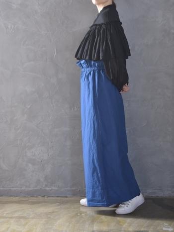 鮮やかな青のカラーパンツは、ゆったりシルエットで履きやすいものをチョイス。黒のブラウス&白スニーカーのベーシックアイテムを合わせて、カラーパンツを主役にしたコーディネートに仕上げています。