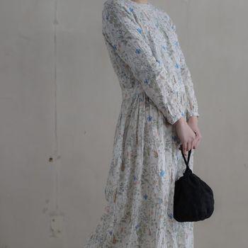 ブルーの小花が映える白系のワンピースに、黒の巾着バッグを合わせて。コーデがバランスよく引き締まって見えます。