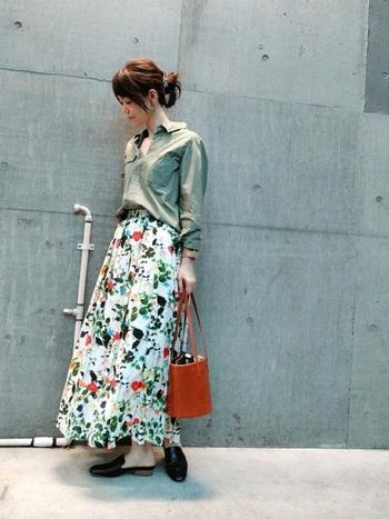 かっこよくなりがちなカーキシャツに、花柄のロングスカートを合わせることでこなれ感が出ています。差し色で赤のバッグを持つことで、全体的に華やかな印象になっています。