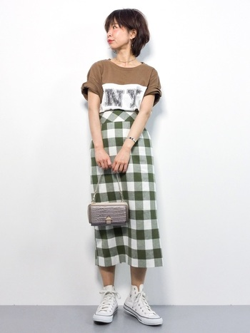 カーキ×チェックで、カジュアルな雰囲気になるスカート。Tシャツやスニーカーでカジュアルコーデにしつつ、バッグで引き締める上級者スタイル。