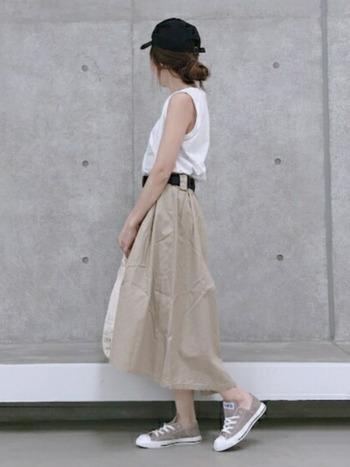 ざっくりとした質感のチノスカート。ベージュの色味がコンバースのスニーカーともよく似合います。黒いベルトとキャップで全体をぎゅっと引き締めて。