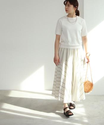 真っ白な半袖のサマーニットは、ストライプデザインの白スカートと合わせてワントーン風の着こなしに。ナチュラル素材のミニバッグやサンダルなど、季節感をアップする小物使いがポイントです。