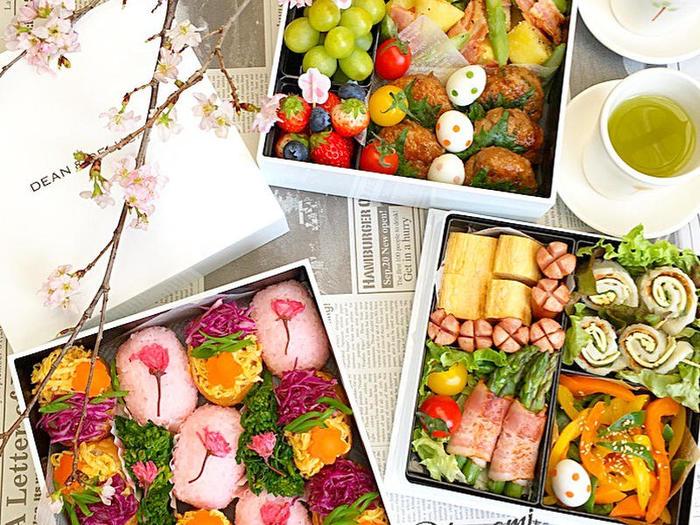 桜の塩漬けをのせたおむすび、三色おいなりさんががかわいいお花見弁当です。おかずも春のアスパラやじゃがいもを使って。配置にも工夫してあり、華やかでお花見がもっと楽しくなるお弁当です。