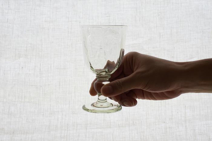 ガラス工房 橙(だいだい)の吹きガラスワイングラス。グラスのあちこちに見える淡い緑は、くるみの色。胡桃の殻を燃やした灰をガラスの原料とまぜ、溶かして使うことで、懐かしい淡い緑の色に仕上がるんだとか…。