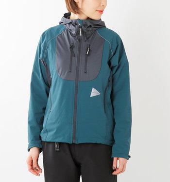「and wander(アンドワンダー)」のトレックフードジャケット。薄手のソフトなストレッチ素材で通気性に優れ、急な小雨にも対応してくれる撥水性がアウトドアシーンにも頼もしい一着です。
