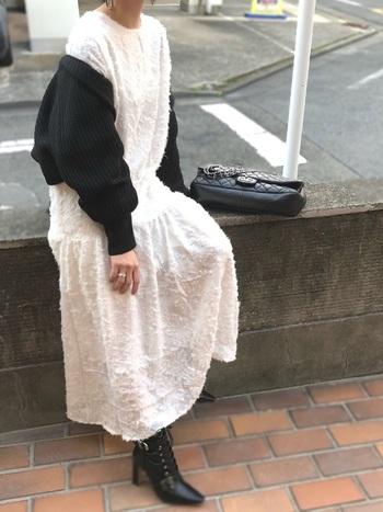 生地感が特徴的な白のドレスワンピースに黒のカーディガンを合わせたお呼ばれスタイル。ただのモノトーンではなく、テクスチャーの遊び心がおしゃれです。足元はレザーブーツでクールにまとめて。