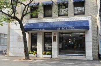 成城学園前駅から徒歩1分。駅前の通りに出ると、白壁と紺色の屋根のコントラストが美しいお店が目に入ります。「成城アルプス」は、1965年創業以来、世代を超えて地元に愛され続けている老舗洋菓子店です。
