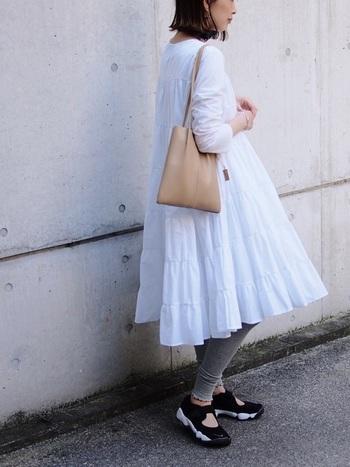 ふんわりとした女性らしい白のティアードコットンワンピースには、グレーの裾フリルレギンスがキュートです。シューズで足元にスポーティーさをミックスして、甘くなりすぎないバランス感がポイント。