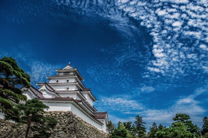 """会津若松のシンボル「会津若松城」、地元では鶴ヶ城と呼ばれています。  戊辰戦争では1ヶ月の攻防に耐え「難攻不落の名城」とうたわれるほどの立派なお城です。 鶴ヶ城の敷地はとても広く、何と東京ドーム6個分!天守閣はもちろん、庭園や茶室などを楽しむこともできますよ。JR会津若松駅から""""まちなか周遊バス""""に乗って約10分とアクセスしやすいのも魅力の観光スポットです。"""