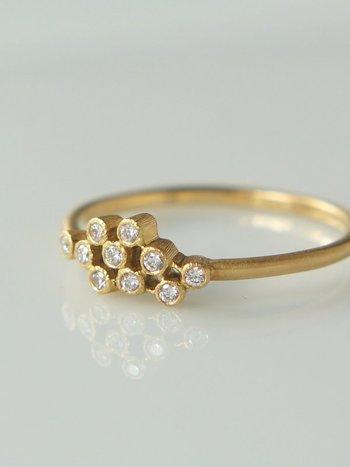リズミカルに踊る泡をイメージさせる、アシンメトリーに並んだダイヤが個性的なリングです。マットな仕上げの地金とのコントラストも絶妙。トップの側面に細かい彫りが入るなど、手仕事ならではの繊細な技が随所に光ります。
