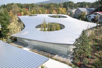 「軽井沢千住博美術館」は、建築界のノーベル賞とも呼ばれるプリツカー賞を受賞した経歴をもつ、西沢立衛氏設計の美術館。  明るく、開放的な、今までにない美術館、というコンセプトのもと、2011年に建てられました。  まるでアメーバのように、伸びやかな一枚屋根が広がり、ところどころに設けられた空洞からは、木々が顔を覗かせます。