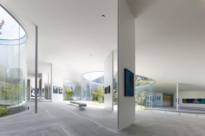 ゆるやかな床の傾斜は、実はこの土地が元々もっていたものだそう。順路が制限されておらず、自由に気の向くままに作品と向き合えるところにも、作り手のおおらかさが感じられますね。  屋内に居ながら、まるで自然の風景の中を散策しているかのように感じられる、のびやかに開かれた美術館です。