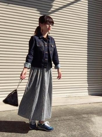 爽やかなギンガムチェックのロングスカートにデニムジャケットを合わせて、可愛らしさもカジュアルさも兼ね備えたコーディネートです。イヤリングや小さめのバッグなど、小物づかいもおしゃれで、参考になりますね。