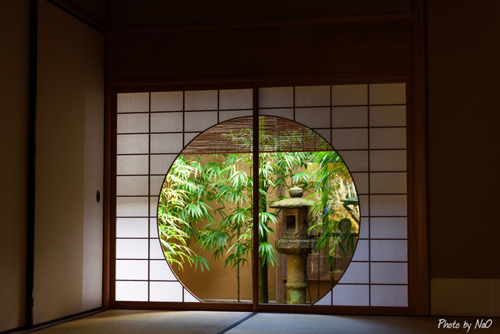 茅葺屋根の外観は、一見すると田舎家風な造り。部屋の中にいても野の趣を感じられるようにと建材にもこだわっています。障子や襖には細やかな技巧を凝らし、丸窓から見える竹の緑が美しく映えます。