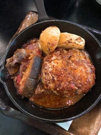 アツアツの鉄板で運ばれてくるハンバーグは、国産黒豚の中でも特にグレードの高い「六白黒豚」を使用しており、スプーンでも食べられるほどのやわらかさが自慢です。
