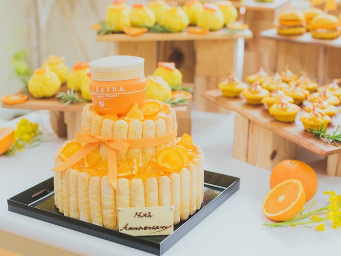 """『バームオレンジ』が誕生してから15周年を迎えるこの春、都内で記念イベントが開かれました。まず目を引いたのは、『バームオレンジ』をモチーフにデコレーションされた、特製のオレンジケーキ。この日集まった来場者たちで、ケーキの前はしばらくの間""""撮影会""""状態となりました。"""