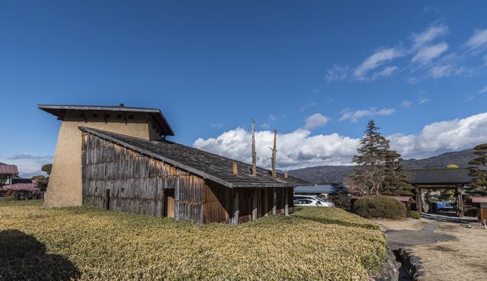 どこか原始的な印象も感じさせるこちらの建物は、「神長官守矢史料館」。茅野市出身でもあり、自然をテーマにした建築をいくつも生み出している、藤森照信氏のデビュー作です。  史料館として設計されたこの建物は、歴史的史料保護のため、実は構造は鉄筋コンクリートでできているんです。ただ、周囲の景観を損ねることがないようにと、地元・諏訪産の石や、藁が入った仕上げ材といった、自然に由来した材料を使用するなど、さまざまな工夫がされた建築です。