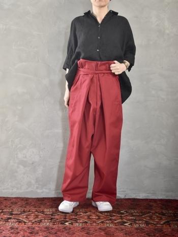 赤のラップパンツは、黒のシャツをフロントだけタックインするトレンド感たっぷりなコーディネートに。ゆったりラフなシルエットながらも、着膨れすることなくスッキリ上品にカラーパンツを着こなしています。