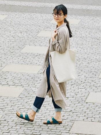 相性のよいパンツスタイルを、ボーイッシュになりすぎずシンプルにまとめたカジュアルコーデ。足元に旬なグリーンを合わせることで、一味違った印象に。 ポイントは、デニムをロールアップして足首をすっきりと見せること。素足でさらっと履いたサンダルが、より女性らしい着こなしを実現しています。