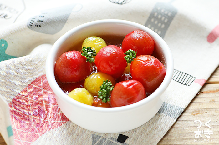 〈冷蔵保存:4日〉 こちらは美味しくて見た目もかわいい「ミニトマトのはちみつマリネ」です。皮を湯むきしてマリネ液に和えるだけで、時短で簡単に作ることができます。彩の綺麗な赤いおかずを一品加えると、お弁当がぱっと明るく華やかな雰囲気になりますよ。