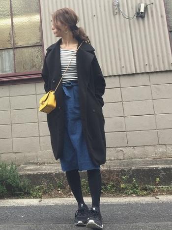 リボンベルトがついた可愛らしいデニムスカート。カジュアルなデニムスタイルながら、リボンがアクセントになってスタイルアップ効果もあります。さりげないリボンなので大人女性でも使いやすく、上品なコーデとも相性抜群。黄色のバッグがいい差し色になっています。