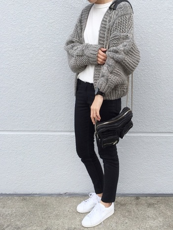 A.P.C.の黒スキニーデニムに、模様編みのざっくりニットカーディガンを合わせたシンプルコーデ。インナーや足元を白でまとめて、上手くバランスを取った着こなしです。