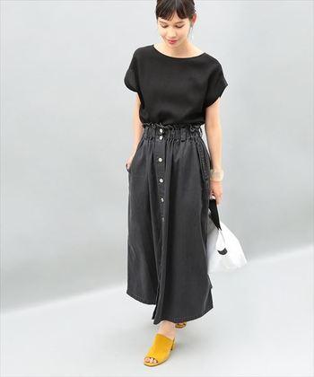 黒デニムのロングスカートに黒ブラウスを合わせたブラックコーデ。フレアなシルエットととろみ系のトップスでクールな印象を和らげています。センター部分に連なるボタンが縦ラインを強調し、ほっそりと見せる効果も。