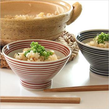 """江戸時代の商人が、くらわんか舟の上で使用していたことから""""くらわんか碗""""と名付けられたお茶碗です。赤と青のボーダーデザインが、どこかレトロさを感じさせます。舟の上でも安定するように、重心が低く持ちやすいシルエットになっているのが特徴。"""