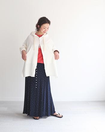 白のオーバーサイズパーカーに、ネイビーのドットスカートを合わせたゆるっとラフなコーディネートです。インナーにさりげなく赤をちら見せして、シンプルになり過ぎない着こなしに。