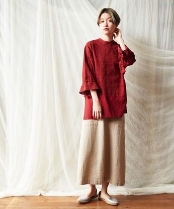 ベージュのロングスカートに、刺しゅう入りのチュニックブラウスを合わせたコーディネートです。繊細なデザインのトップスも赤を選べば甘くなり過ぎないので、大人の女性でも着こなしやすいですね。