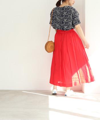 リネン素材の赤スカートは、モノトーンの柄トップスと合わせてちょっぴりスパイシーな着こなしに。スカートが主役のコーディネートなので、黒系のトップスを合わせても地味にならないのがポイントです。