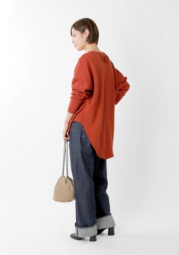 後ろが長くなっている赤のロング丈トップスは、デニムワイドパンツに合わせてルーズな着こなしに。ヒールのシューズを合わせることで、女性らしいワンポイントをプラスしています。