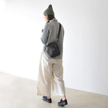 黒のシンプルなショルダーバッグは、ニットベストと白のワイドパンツに合わせてカジュアルに。ニット帽やスニーカーを合わせた大人のスポーティーミックススタイルには、ショルダーバッグがぴったりですね。