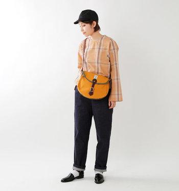 オレンジのショルダーバッグを、オレンジのブラウスとデニムパンツに合わせたコーディネート。撥水性の高いショルダーバッグとキャップを合わせて、アウトドアスタイルにもぴったりの着こなしですね。