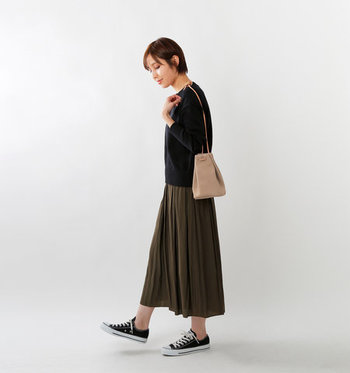 レザー素材の巾着ショルダーバッグを、黒トップスとカーキのプリーツスカートにオン。明るめのベージュが、ダークトーンアイテムのよいアクセントカラーになっています。
