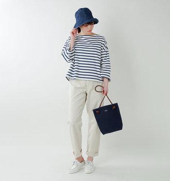 カジュアルに使える帆布ショルダーバッグは、ネイビーをボーダートップスと白パンツに合わせてマリン風スタイルに。デニムの帽子もバッグと色が合っているので、統一感のあるコーディネートが楽しめます。