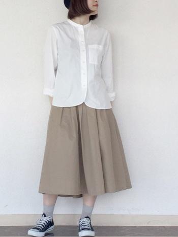 白シャツ×ベージュスカートのスタンダードなスタイリングに、バンドカラーのシャツを合わせてさり気なく変化をプラス。トップスはあえて外に出して、独自のディティールを楽しみましょう。