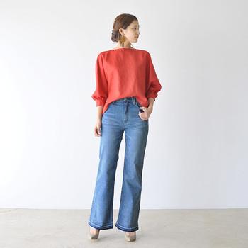 赤系のボリューム感があるトップスに、ワイドシルエットのブーツカットジーンズを合わせたコーディネートです。フロント部分を少しだけタックインして、ワイドシルエットのアイテム同士でももったりさせないのが着こなしのポイント♪