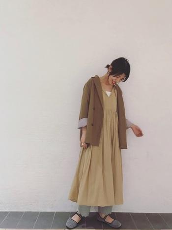 ベージュのゆったりワンピースに、細身のグレーのリブパンツを合わせて。レギンス感覚でスカートやワンピースとの重ね着を楽しめます。