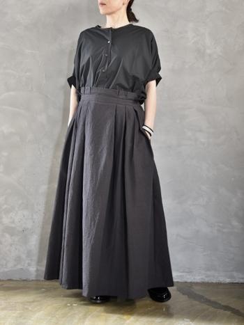 """半袖の黒シャツ、脱""""メンズライク""""ならスカートを合わせたい。全身シックなカラーコーディネートなら、半袖が抜け感を作ってくれておしゃれに見えます。"""
