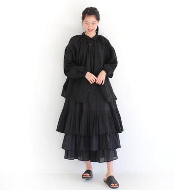 ふんわりした袖や身頃のシルエットが女性らしい黒シャツです。同じくふんわり形のティアードスカートを合わせてシルエットに可愛らしさを。