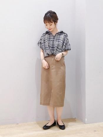 黒のチェックシャツとベージュのナロースカートを合わせたコーディネートは、トップスイン&抜き襟で清楚な印象に。品のいい組み合わせは、オフィスカジュアルコーデとしてもおすすめです。