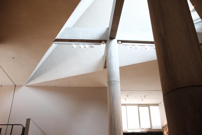 """ここは、建物の中心に置かれれた「19世紀ホール」。建物を支える柱や梁には、木の型枠にコンクリートを流し込んだ""""姫小松""""の美しい木目を見ることができますよ。三角形のトップライトから差し込むやわらかな自然光は、作品たちをより印象的に見せてくれます。"""