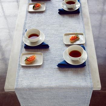 リネン素材のテーブルランナーはとても涼し気で、軽やかな雰囲気です。ティーカップの下に濃いブルーのクロスを畳んで敷きこむことで、リズミカルなアクセントが生まれました。