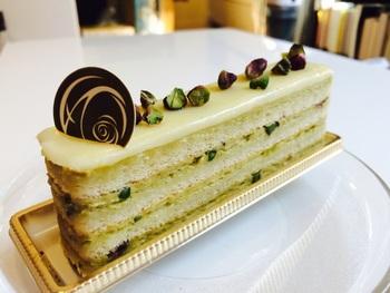 ホワイトチョコレート・ピスタチオのバタークリーム・ダークチョコレートのガナッシュ・ジョコンド生地の13層が重なる『オペラピスタチオ』。