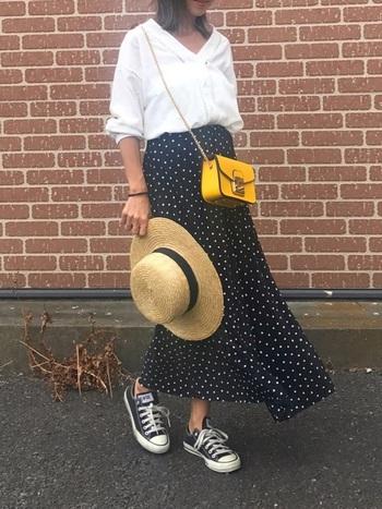 Vネックのデザイン白シャツにドットのスカートを合わせて。イエローの小ぶりなバッグがコーデに華を添えるアクセントに。