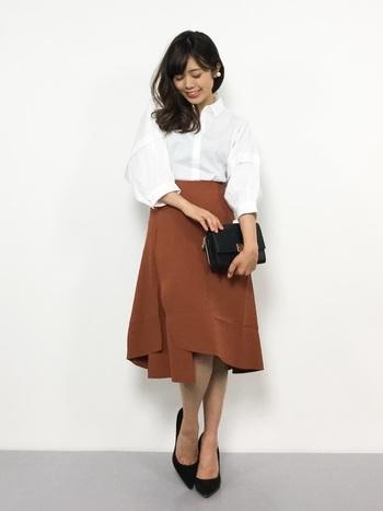 ボリューム袖のフェミニンな白シャツにブラウンのスカートを合わせて。オフィスにも着ていけるキチンと感あるコーデです。